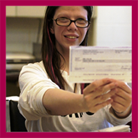 Woman holding check from employment earnings.