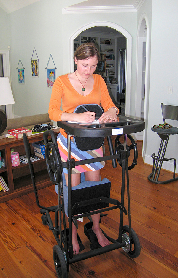 Woman standing in an assistive wheelchair and writing on an attached desktop.