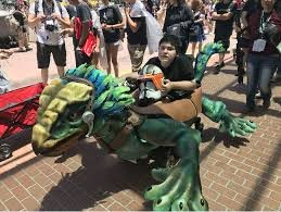 Boy sitting in his fabricated dragon wheelchair cover.