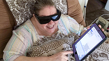 Blind woman listening to a conversation on her iPad.