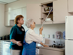 Aide helping an older woman reach for a can on a top kitchen shelf with the assistance of a gripper.