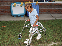 Young girl using a walker to navigate a course outside at school.