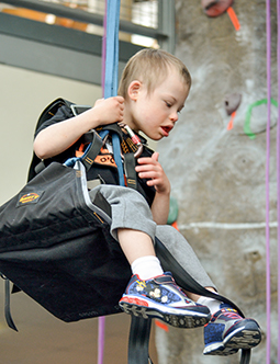 Young boy in an adaptive climbing seat at a climbing wall event.